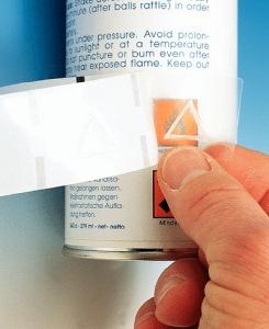 Hand die ein Warnsymbol für Blinde auf eine Spraydose klebt