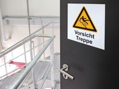 Tür mit Warnschild 'Vorsicht Treppe'