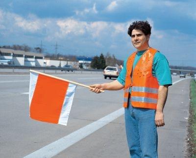 Bauarbeiter mit warnflagge am straßenrand
