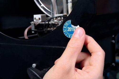 Materialbild zeigt den Versuch die Papier Plakette vom Objekt abzulösen diese zerreißt gleich
