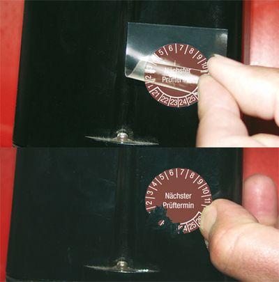 Übertrag der Plakette mit einer Folie. Nach Verklebung zerreißt Plakette in kleine Stücke