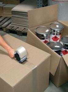 Paket wird mit einem Paketbandabroller verschlossen