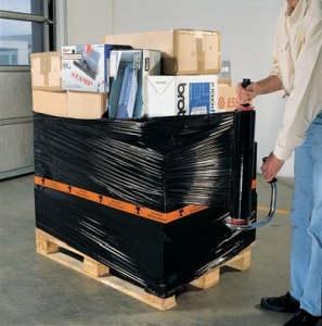 Arbeiter umwickelt eine Palette mit Kisten mit schwarzer Stretchfolie