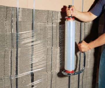 Arbeiter wickelt durchsichtige Stretchfolie mit einem Handabroller um eine Palette