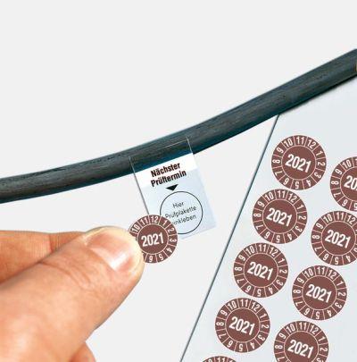 Eine Prüfplakette wird auf ein Kabel-Grundetikett geklebt