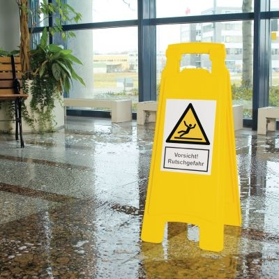 Gelber Warnaufsteller mit Warnsymbol und Text Vorsicht Rutschgefahr auf feuchtem Bodem