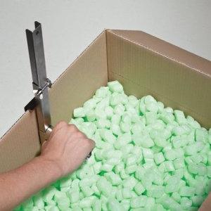 Mit einem Wellkartonriller wird bei einem Wellpappkarton auf Höhe des Füllmaterials eine zusätzliche Falzkante eingeritzt