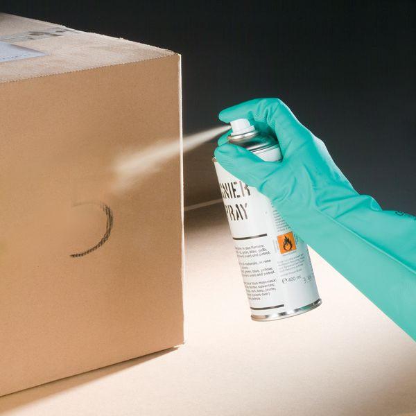 Beschriftung auf Karton wird mit Adeckspray besprüht
