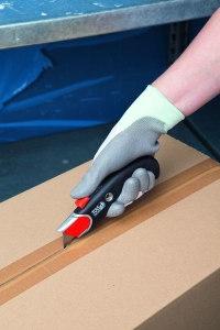 Paket wird mit einem Sicherheits-Kartonmesser geöffnet
