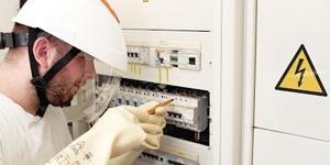 Electricien avec casque de protection et gants isolants