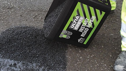 A pothole in the ground is being fixed immediately by using a Instant Pothole Repair ready mixed formula.