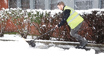 A man wearing personal protective equipment which includes a reflective yellow hi-vis vest and black safety boots. He is shoveling a large amount of snow outside using a yellow and black One-Man Snow Plough.