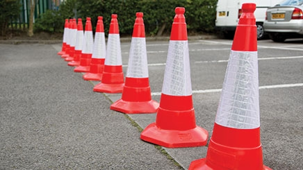 Ten red JSP® Sand Weighted One Piece Traffic Cones with high visibility sleeves are in a car park in a row horizontally restricting access to certain parking bays.