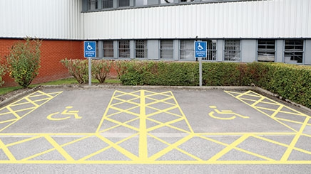 A car park which has two designated disabled parking bays. The disabled parking bays have been created using yellow line marking paint and there are two blue and white 'disabled parking only' car park signs on a grey post in front of the parking bays.