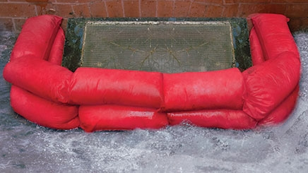 Two red HydroSnake Flood Prevention barriers are being used to stop flood water entering a drain.