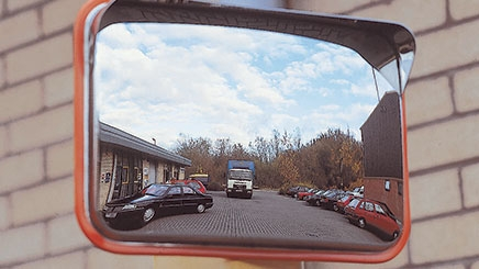 A red Anti-Vandal Traffic Mirror has been post mounted in a car park. In the reflection of the mirror you can see many cars parked and a large lorry parked in the middle of the car park.
