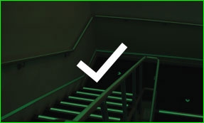 Glow in the dark tape on stairs with a check icon