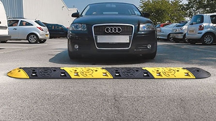 Black car approaches a black and yellow Seton Speed Bump in a car park