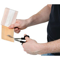 A man using medical shears to cut a plaster
