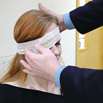 Casualty being dressed with eye pad medical dressing